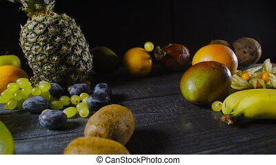 Grapes Falling on Wooden Table With Tropical Fruits - Grapes...