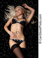 Blond in black lingerie covered in diamonds - A slim woman...