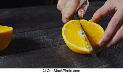 Orange Fruit Being cut and It's Splatters Juice on Dark...