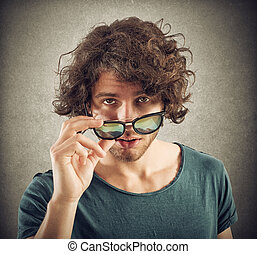 Look over sunglasses - Boy lowers his sunglasses and looks...