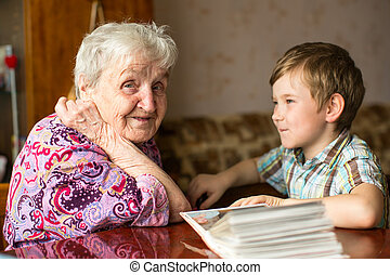 Happy grandma sits with his young