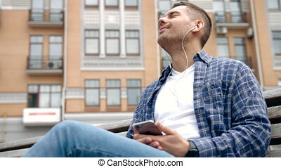 Close up of a young man sitting outdoors listening to music.