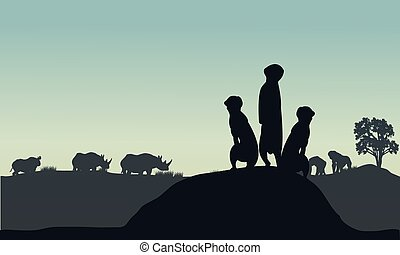 Silhouette of meerkat and rhino in the hills