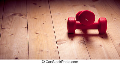 Red loght dumbbells on a wooden flor