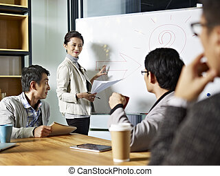 young asian business woman facilitating a discussion - young...