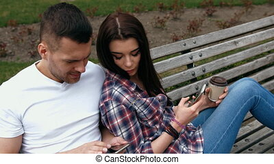 ouple sitting on a bench using mobile phone or digital...