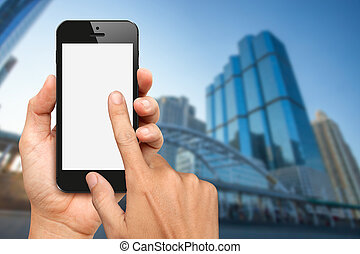 Hands hold and touch smart phone with office buiding...