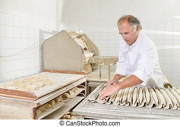 Baker preparing baguettes for the oven
