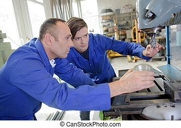 Two men looking at industrial drill