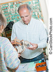 Cobbler looking at a womens damaged shoes