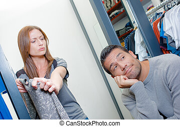 Bored man waiting for his wife in a shop