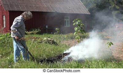 Female senior gardener burn grass and refuse in fire on...