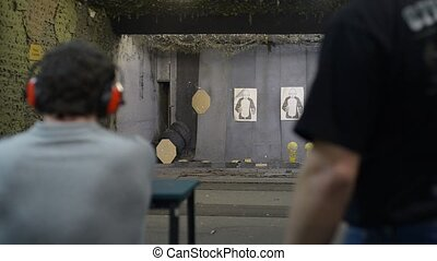 a man shooting at a shooting range with a pistol