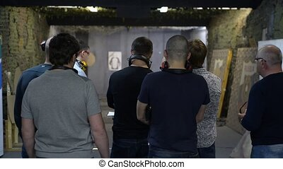 a group of men standing on a shooting range, indoor