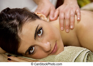 Beautiful woman relaxing in spa getting massage in vacation...