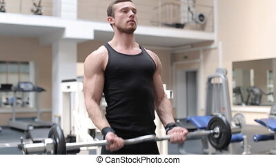 Bodybuilder shakes his biceps at the gym