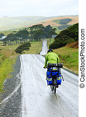 Travelling cyclists - Cycle tourists on a dirt road in New...