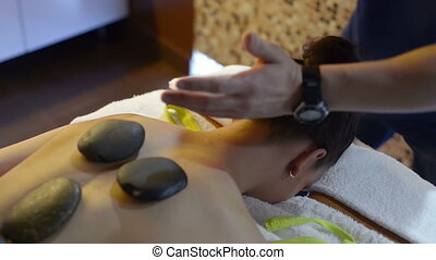 Masseuse using hot stone massage therapy on a beautiful...