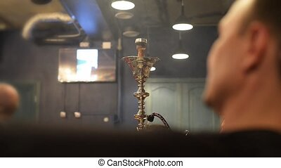 Men smoke shisha in the bar, background