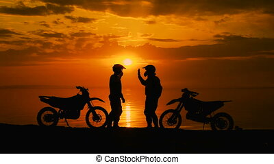 Two motorcyclists at sunset communicate. They are naberegu...
