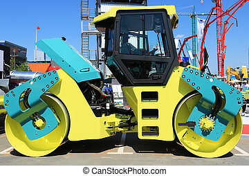 Compactor roller compacting asphalt on a background of...