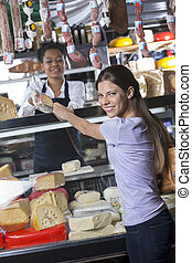 Happy Woman Buying Cheese From Worker At Shop