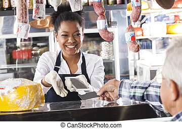 Happy Saleswoman Accepting Mobile Payment From Customer