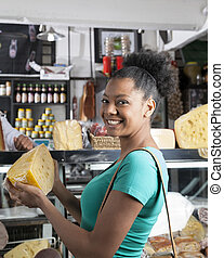 Happy Woman Buying Cheese In Grocery Store