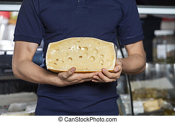Man Holding Cheese In Grocery Store