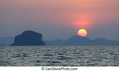 Beautiful sunset at sea - Sun goes behind the mountain for...