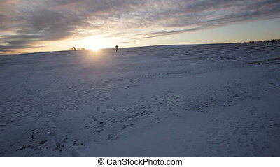 Cross-country skiing on field. - Two girl on cross-country...