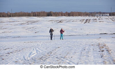 Cross-country skiing on field. - Girls on cross-country skis...