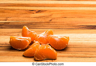 Tangerine Pieces - A tangerine peeled and pulled apart on a...