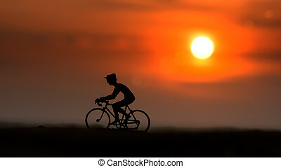 Silhouettes cyclists on the beach at sunset.