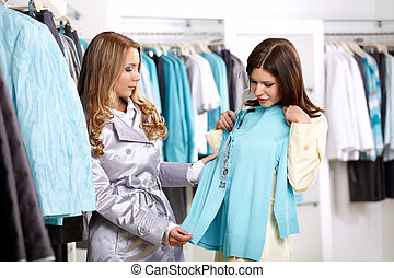 Shoping - Two girls consider a jacket in shop