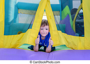 Curious boy looking from entrance of bouncy house - Single...