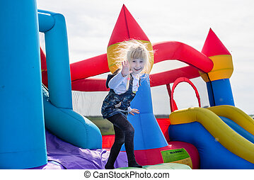 Excited girl waving from inflatable bouncy slide - Single...