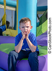 Boy with sweaty face sitting near bouncy house - Exhausted...