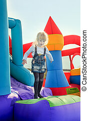 Happy girl at bottom of inflatable bouncy slide - Single...