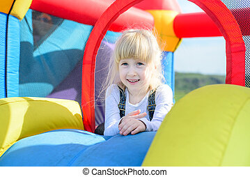 Happy girl on top of giant bouncy slide - Cute little happy...