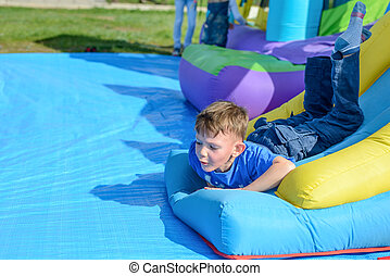 Handsome little boy lies on a bouncy castle