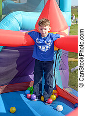 Handsome little boy standing on a bouncy castle surrounded...