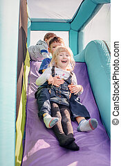 Children going down inflatable bouncy slide - Adorable young...