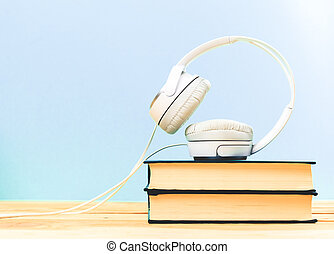 Books on the table with headphones put on them - Concept of...
