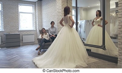 Women having fun during bridal gown fitting in wedding...