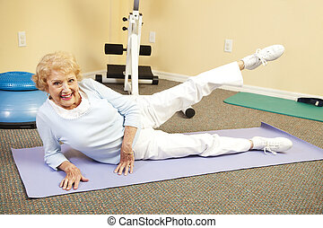 Senior Stretching - Fit happy senior woman doing stretching...