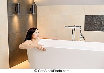 brunette woman relaxing in bath - Young attractive brunette...