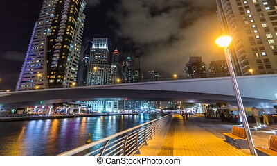 Walk on promenade of Dubai Marina with view of Towers and...