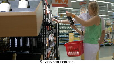 Family couple buying wine in supermarket - Young man and...