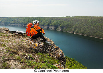 Cyclist in Orange Wear Sitting on Rocky Hill - Cyclist in...